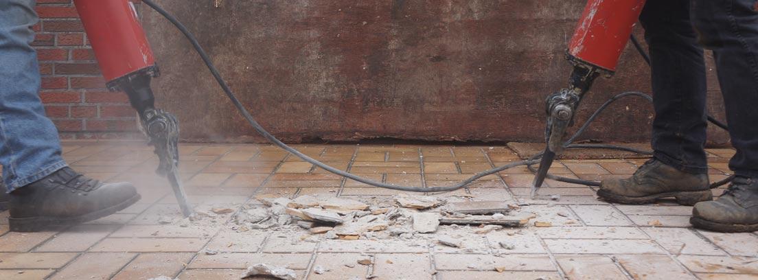 Don hombres con martillos demoledores quitando el suelo de una vivienda por una avería general