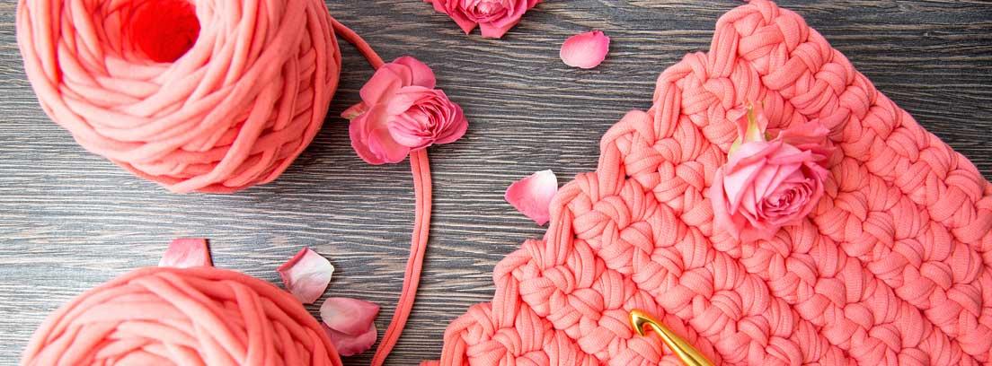 Ovillos de trapillo rosa junto a una alfombra de trapillo