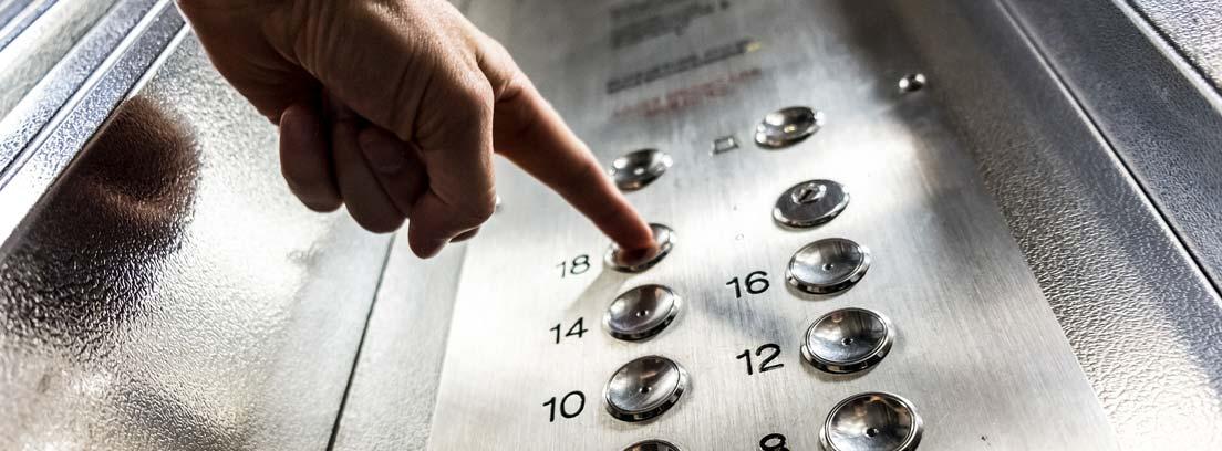 Mano pulsando el botón de un ascensor