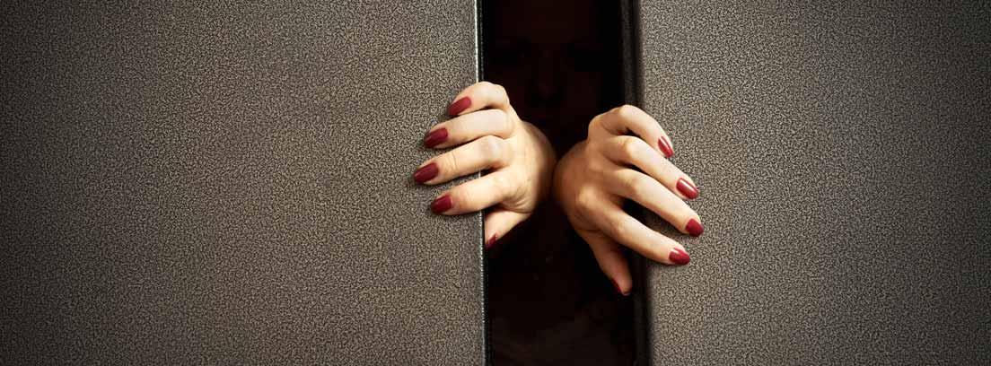 Manos forzando la apertura de puertas de un ascensor