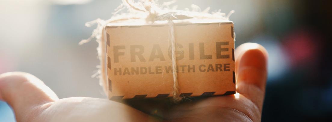 Mano con caja de cartón de regalo hecha de reciclaje.