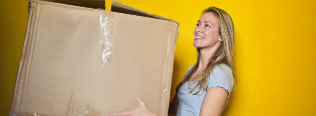 Mujer con una gran caja de cartón sujeta entre sus manos.