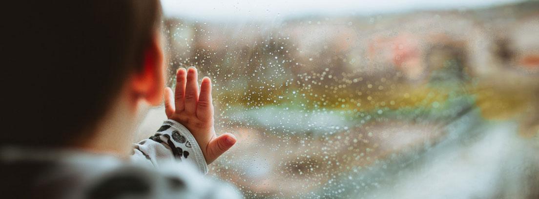 Niño con las manos sobre un cristal con vaho y gotas de lluvia.
