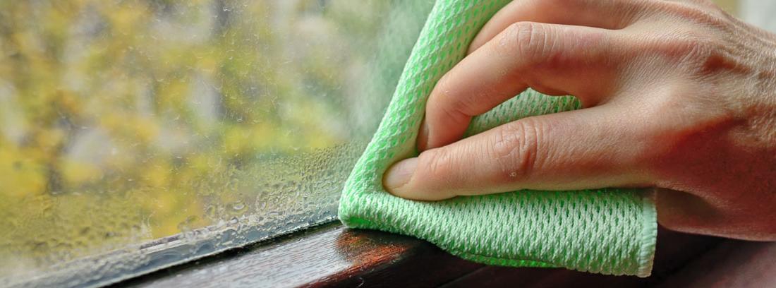 Mano con una bayeta limpiando moho por condensación de una ventana