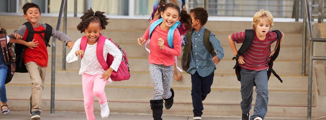 niños corriendo con sus mochilas tras salir del colegio