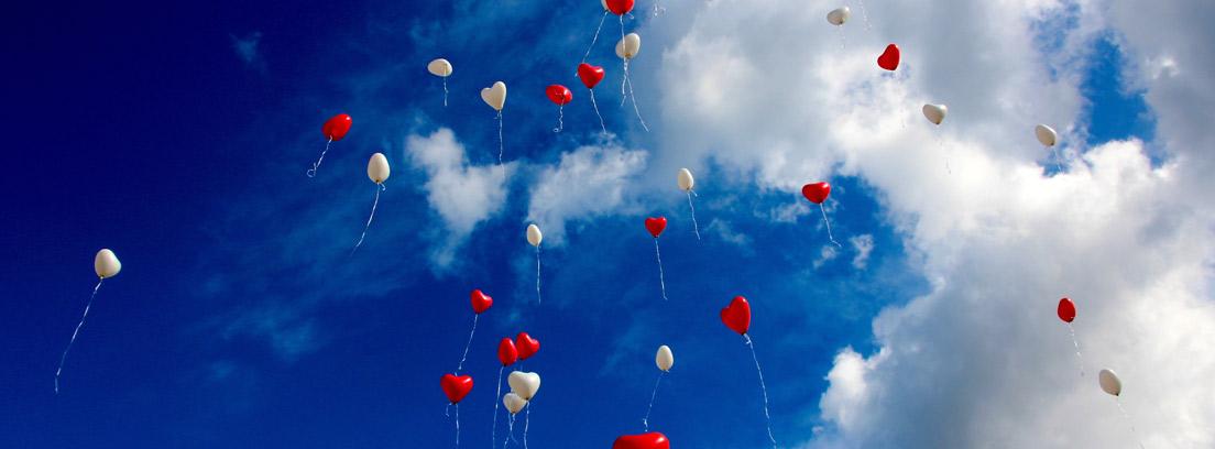 Globos en forma de corazón blancos y rojos por el cielo azul y con nubes blancas