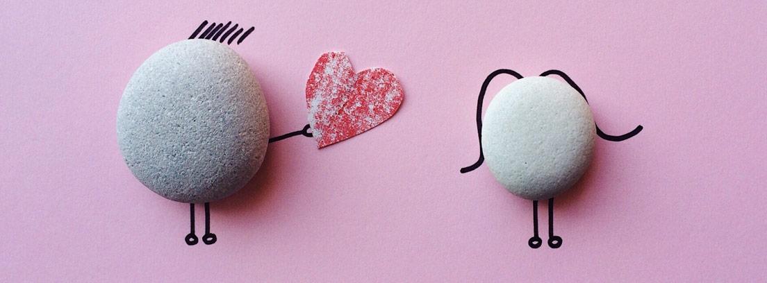 Piedras sobre fondo rosa con brazos y piernas pintadas y entregándose un corazón.