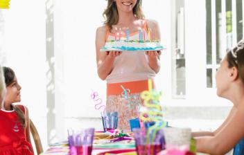 mujer llevando una tarta en un cumpleaños infantil
