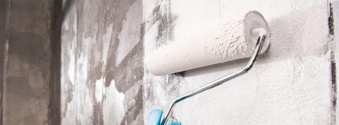 Mano con rodillo pintando pared en color blanco