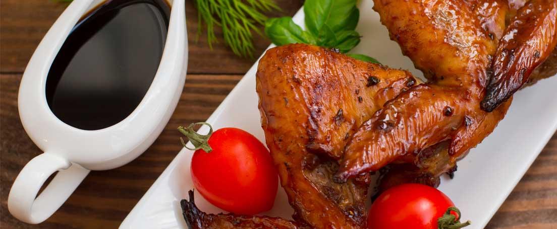 Bandeja de alitas de pollo al horno junto a salsera con salsa de soja con miel