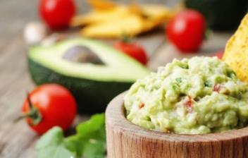 Salsa guacamole en un cuenco de madera con un nacho junto a tomates, limas y aguacates