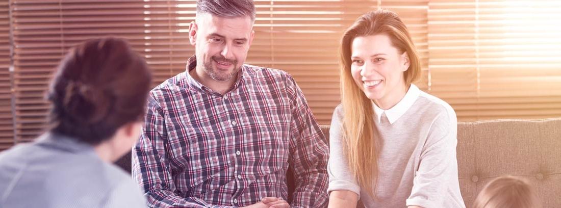 Hombre y mujer sonrientes en una tutoría en el colegio hablando con otra mujer