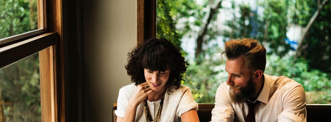 Hombre y mujer sentados a una mesa mirando un teléfono móvil
