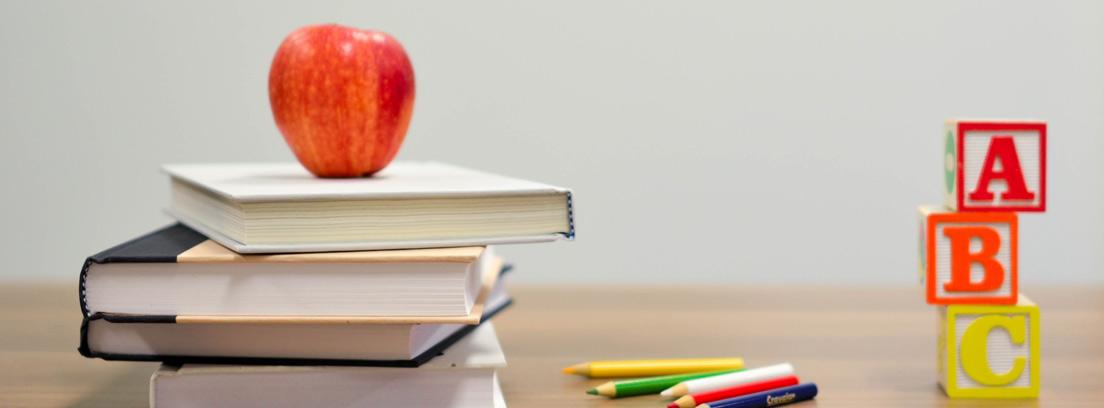 Montón de libros con una manzana, lápices de colores y bloques de letras sobre una mesa
