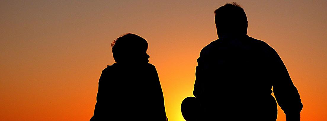 Silueta de un hombre y un niño sentados juntos mirando el atardecer