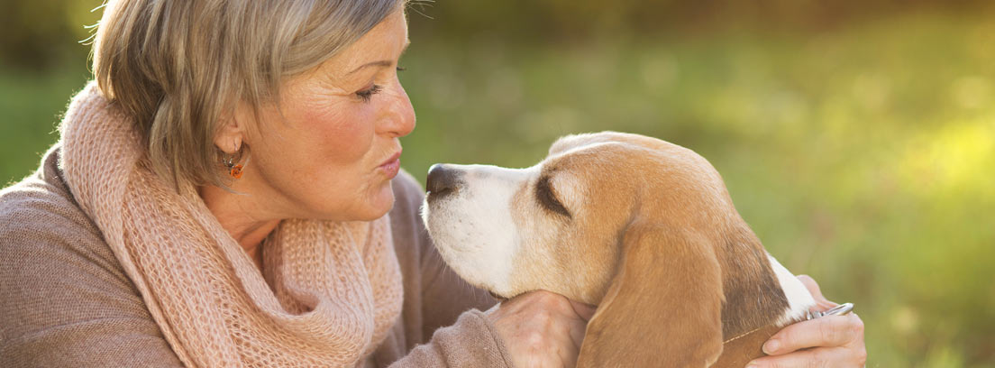 Mujer dando un beso a su perro