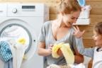 Niña abraza a mujer junto a lavadora abierta con ropa caída.