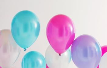 Varios globos de helio de color azul, morado y blanco