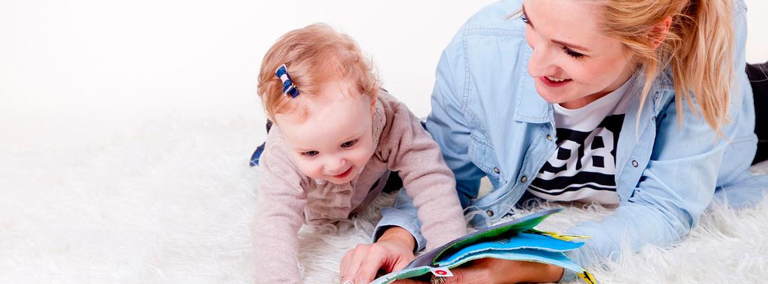 Chica leyendo un cuento a un bebé sonriente