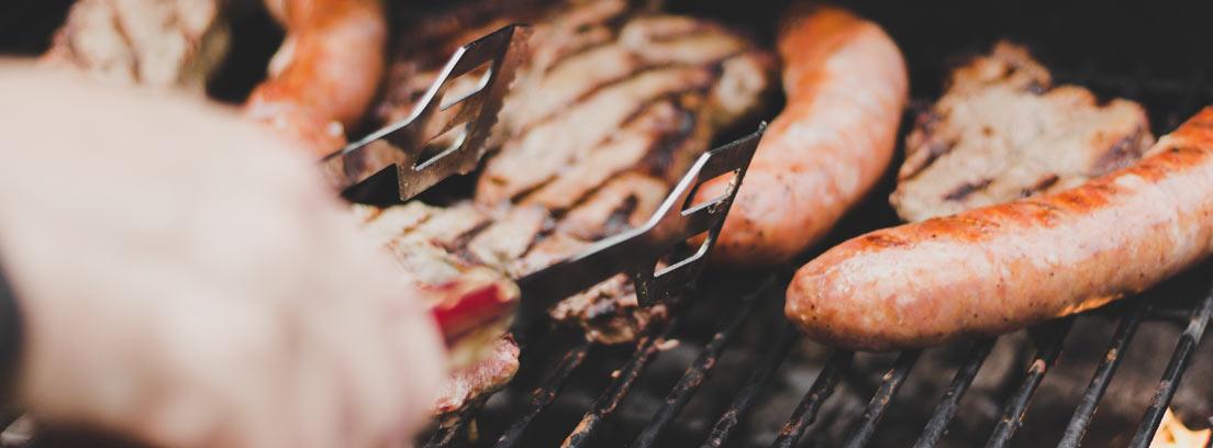 Primer plano de una mano sujetando carne en la barbacoa con unas pinzas
