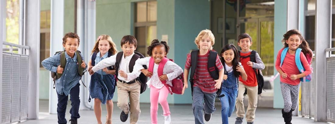 Grupo de niños con mochilas corriendo por un pasillo
