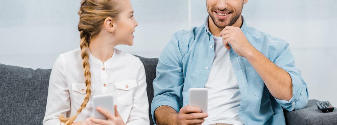 Hija y padre con sendos móviles sentados en un sofá.