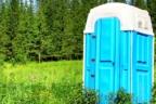 Inodoro ecológico dentro de caseta azul en medo de un bosque