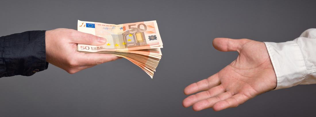 Mano extendiendo un fajo de billetes de 50 euros a otra mano