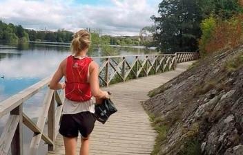 Mujer corriendo junto a un lago con bolsa de basura en la mano.