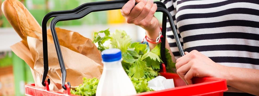 Mujer sujetando una cesta con lechuga, pan y leche tras hacer la compra eligiendo productos saludables