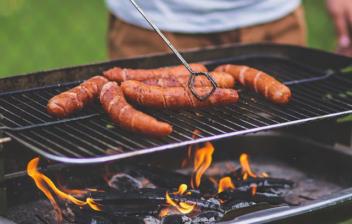 Barbacoa rectangular con brasas y llama con rejilla con salchichas