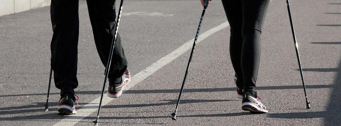 Dos mujeres de espaldas practicando Nordic Walking por una ciudad
