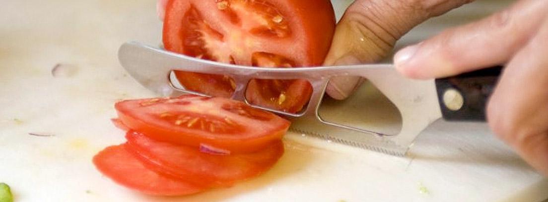 Mano con cuchillo cortando un tomate en rodajas