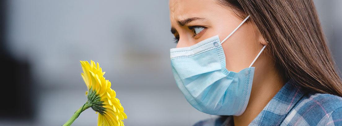 Mujer con mascarilla mirando con terror una flor