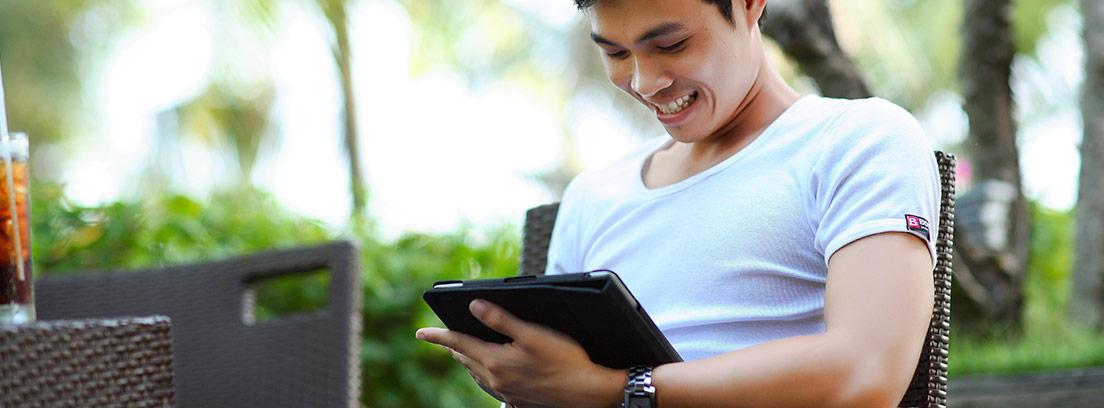 Hombre sonriente mira hacia tableta que tiene la mano.
