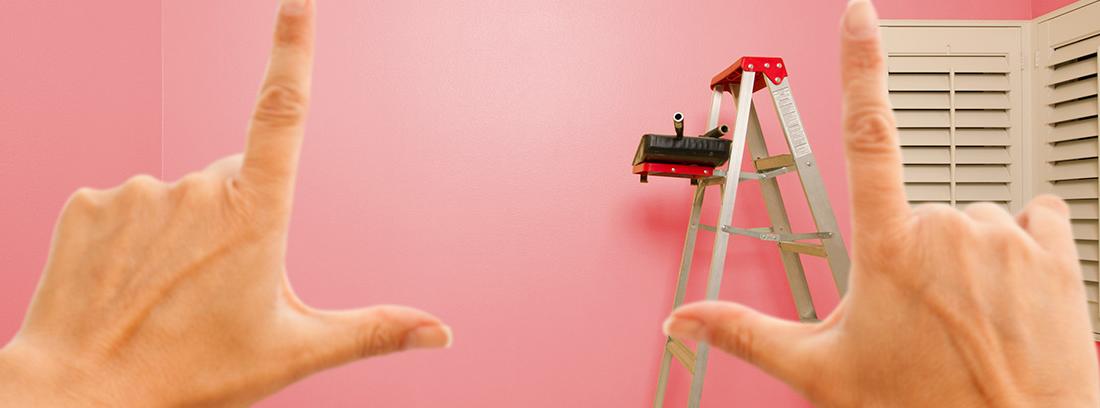 Manos enmarcando una pared pintada de rosa