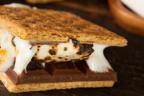 Smore en primer plano sobre mesa de madera con chocolate y nube blanca.