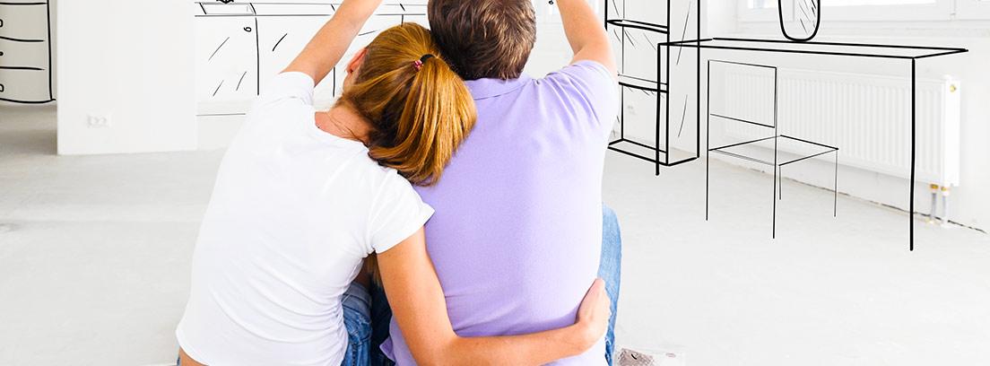 Hombre y mujer sentados de espalda miran paredes blancas con dibujos de muebles