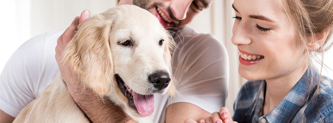 Pareja joven abrazando a un perro