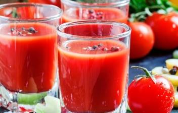 Varios vasos con cóctel Bloody Mary junto a tomates.