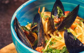 bol azul con espaguetis con mejillones y tomate y unas ramitas de perejil
