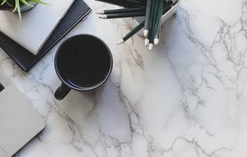 Vista cenital de una encimera de mármol con un ordenador y una taza de café