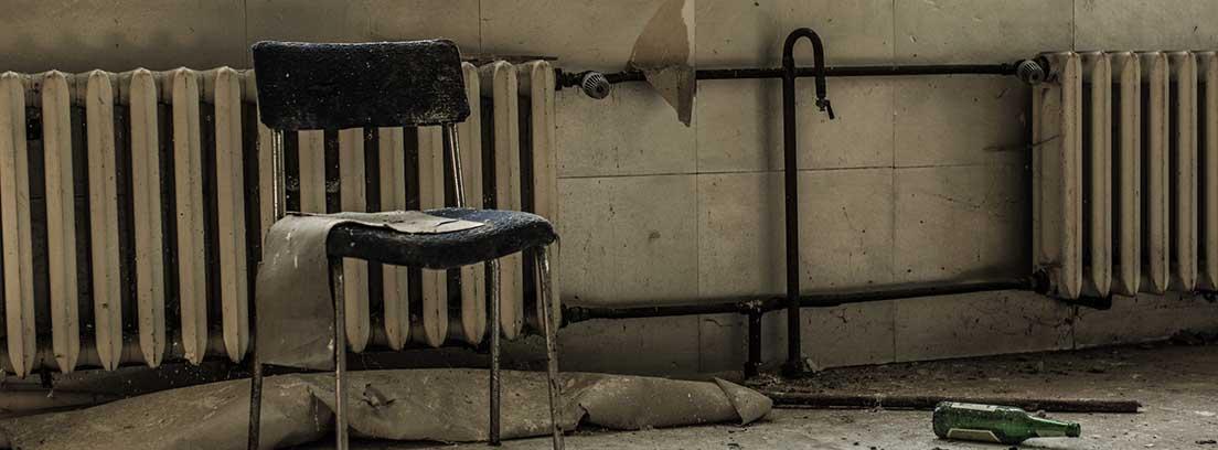 Silla vieja delante de unos radiadores oxidados