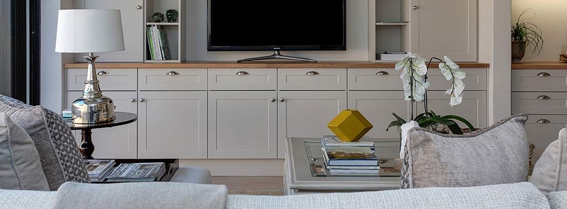 Televisión en salón rodeada y sobre muebles lacados en color blanco y sillones.