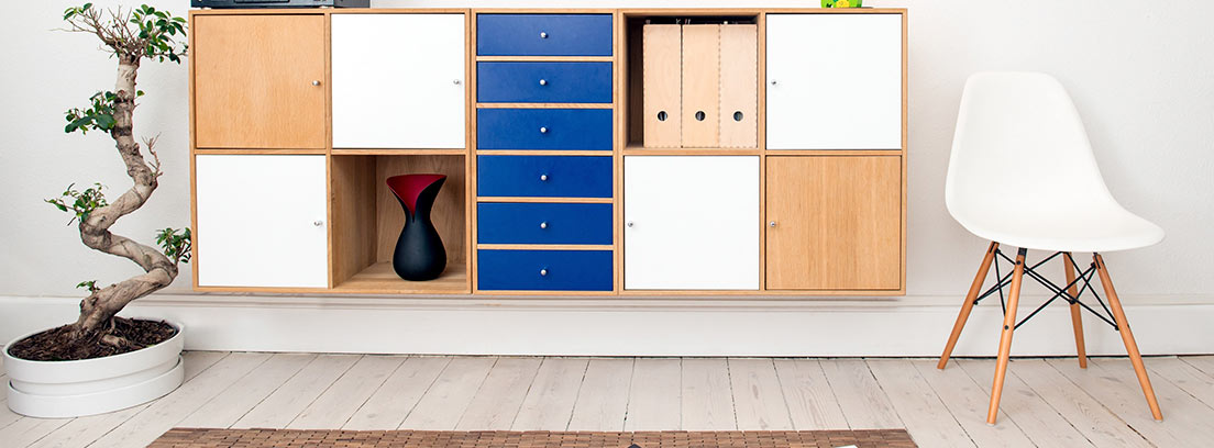 Mueble bajo dos cuadros con cajones y huecos y varios colores.