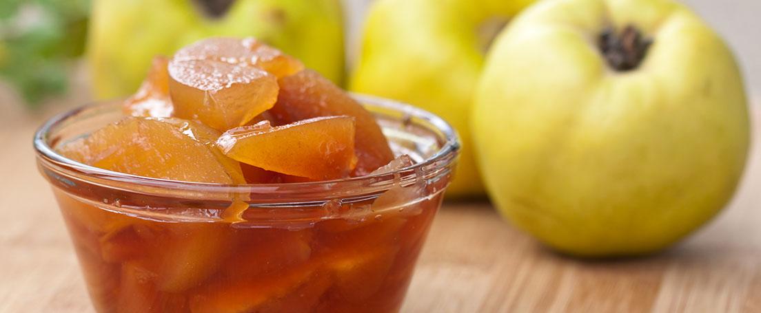 Cuenco con dulce de membrillo y fruto al fondo