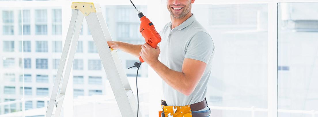 Hombre con casco amarillo y cinturón de herramientas con taladro en la mano