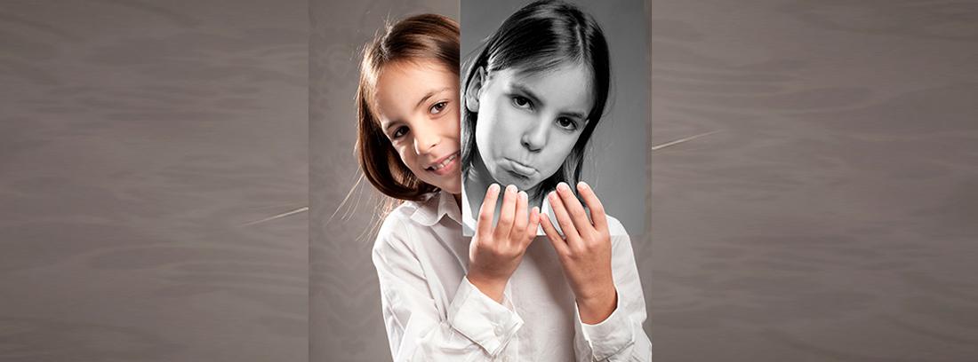 Niña sonriente sujetando una foto suya con gesto triste