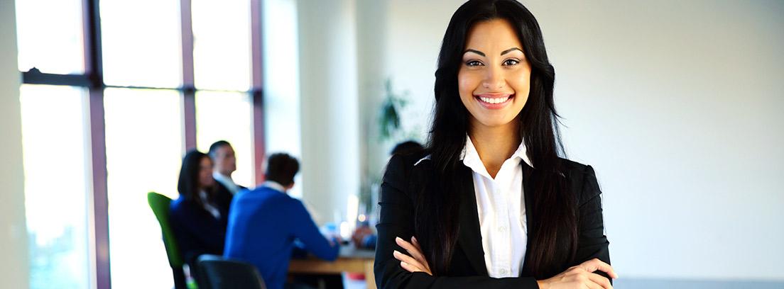 Mujer sonriente con traje y los brazos cruzados en una oficina