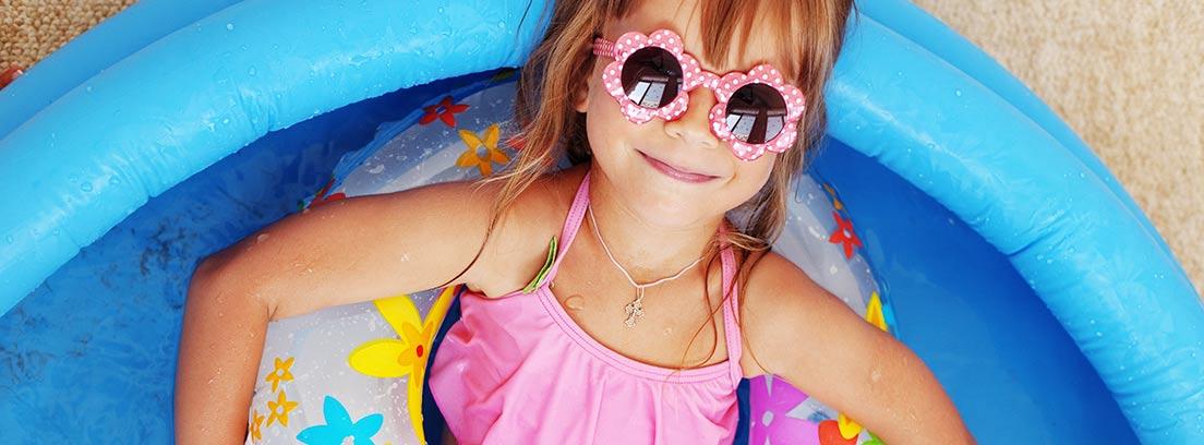 Niña con gafas de sol y flotador dentro de una piscina barata desmontable